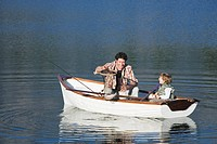 Father and son 4_7 sitting in rowing boat on lake, fish caught in net