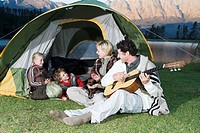 Young Family camping, sitting in front of tent with father playing Guitar