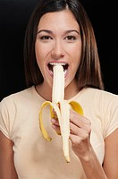 Portrait of a woman eating a banana
