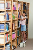 Schoolgirl 10-13 standing in library stretching to put book in bookshelf (thumbnail)