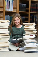 Girl 10-13 in library, reading and sitting between two piles of school books (thumbnail)