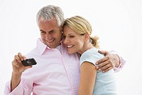 Mature couple smiling while looking at photos on camera phone