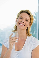 Mature woman smiling and holding glass of water