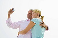 Mature couple taking self portrait with digital camera, smiling