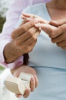 Mature couple, man putting diamond ring on woman's finger, detail of hands