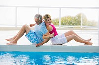 Senior couple sitting back to back on edge of swimming pool, laughing