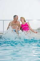 Senior couple sitting on edge of swimming pool laughing and splashing