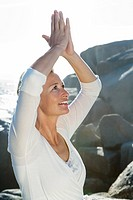Mature woman arms raised above her head doing Yoga exercises, side profile