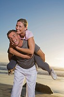 Senior couple having fun on beach, man carrying woman piggyback