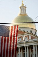 American flag illuminated by light from Massachusettes State House, with dome contstructed by Paul Revere