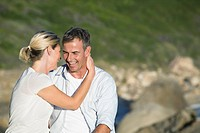 Mature couple sitting on rock, embracing and talking, smiling, portrait