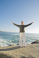 Man standing on cliff with arms outstretched, smiling with waves in background