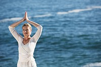Mature woman arms raised doing Yoga exercises with ocean in background