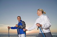 Senior couple wearing tracksuit doing Nordic Walking on beach at sunset
