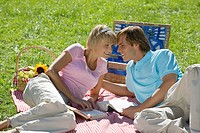Young couple lying on picnic Blanket, looking at each other