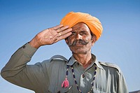 Man wearing a colourful saffron turban and saluting at Osian Camel Camp, Osian, Rajasthan, India
