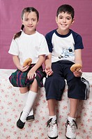 Boy and his sister holding donuts and smiling