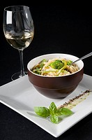 Close_up of green pepper and broccoli macaroni with a glass of white wine