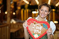Young woman holding Gingerbread heart at Oktoberfest, Munich, Germany (thumbnail)