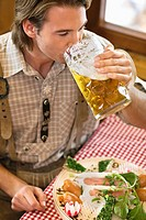 Close_up of young man drinking beer at Oktoberfest, Munich, Germany