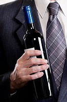 Businessman holding a wine bottle
