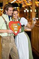 Young couple taking self_portrait at Oktoberfest, Munich, Germany