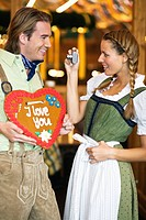 Young man with gingerbread heart posing for photo at Oktoberfest, Germany