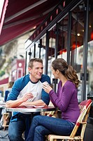 Young couple sitting outside street side cafe, drinking coffee, Paris, France