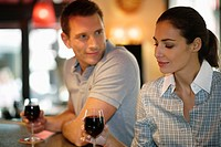 Young couple drinking red wine in cafe, Paris, France