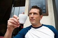 Young man drinking coffee outside street side cafe, Paris, France