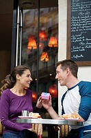Young couple outside street side cafe, man giving woman present, Paris, France