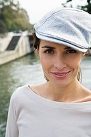 Young woman wearing beret by river Seine, Paris, France