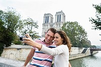 Young couple in front of Notre Dame Cathedral, woman taking photo, Paris, France