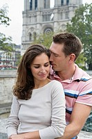 Young couple hugging in front of Notre Dame Cathedral, Paris, France