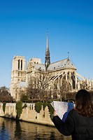 Woman looking at map with Notre Dame Cathedral in background, Paris, France