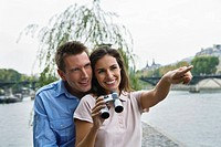 Young couple by riverside, woman holding binoculars and pointing, Paris, France