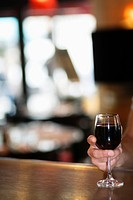 Close up of man holding glass of red wine at cafe bar, Paris, France