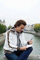 Young man sitting on Pont Neuf bridge, writing postcard, Paris, France