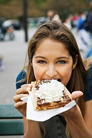 Young woman eating cream and chocolate covered Waffle, Paris, France