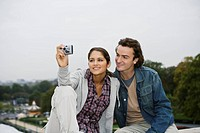Young couple sitting on wall, woman taking photo, Paris, France (thumbnail)