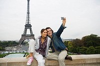 Young couple sitting on wall, man taking photo, Eiffel tower in background (thumbnail)