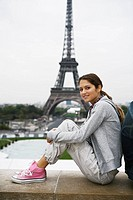 Young couple sitting back to back on wall, Eiffel tower in background (thumbnail)