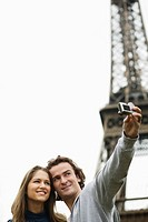 Young couple in front of Eiffel tower man taking photo, Paris, France