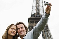 Young couple taking self portrait in front of Eiffel tower, Paris, France (thumbnail)