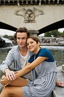 Young couple embracing on steps by river Seine, Paris, France