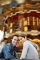 Young couple sitting on bench with Carousel in background, Paris, France (thumbnail)