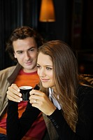 Young couple in street cafe, woman drinking coffee, Paris, France