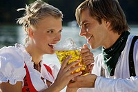 Young couple in traditional Bavarian outfit, sharing beer in beer garden, Munich