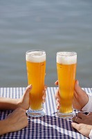 Close-up of young couple drinking beer in Seehaus, beer garden, Munich, Germany (thumbnail)