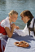 Young couple in traditional Bavarian outfit, arm_wrestling in Beer garden